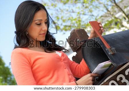 hispanic woman checking mailbox