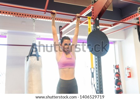 Hispanic woman exercising intensely for greater strength in health club