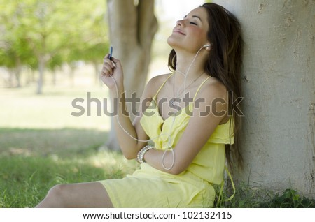 Hispanic woman listening to music and relaxing at the park