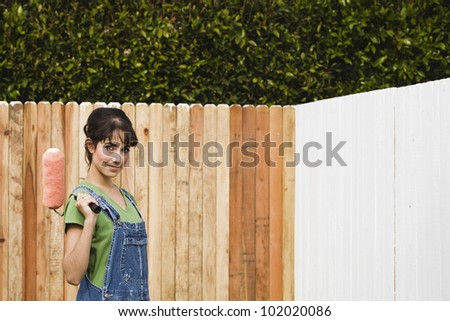 Hispanic woman painting fence