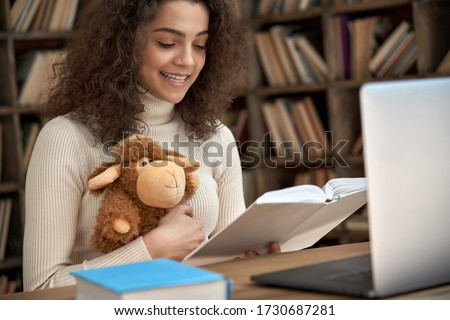 Hispanic woman remote kids teacher reading fairy tale book teaching online. Young happy latin girl holding book and toy looking at laptop computer webcam. Distance children video call zoom education.
