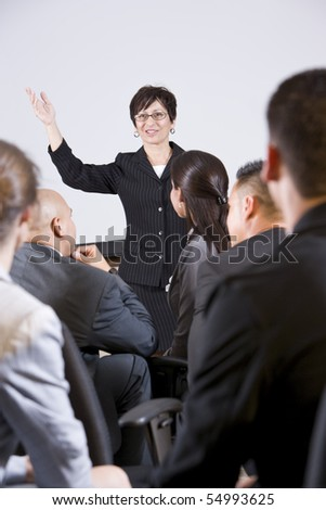Hispanic woman standing in front, speaking to group of business people