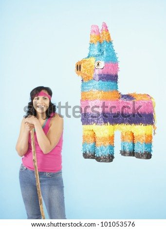 Hispanic woman standing next to pinata