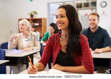 Hispanic woman studying at adult education class looking up