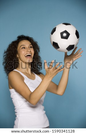 Hispanic woman tossing soccer ball in air