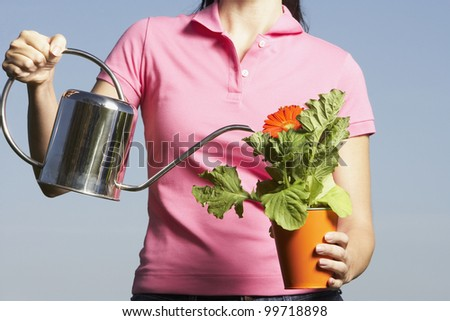 Hispanic woman watering potted plant