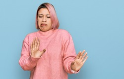 Hispanic woman with pink hair wearing casual winter sweater disgusted expression, displeased and fearful doing disgust face because aversion reaction.