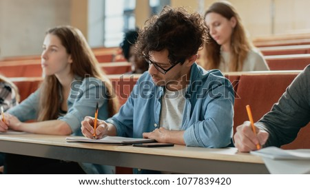 Hispanic Young Man Among His Fellow Students in the Classroom. Young Bright People Listening to a Lecture and Take Notes while Studying at the University.