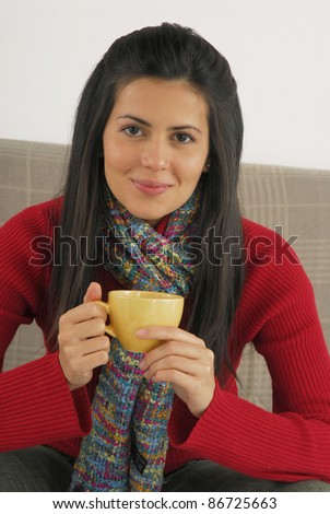 Hispanic young woman drinking coffee or tea at home.