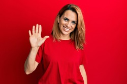 Hispanic young woman wearing casual red t shirt showing and pointing up with fingers number five while smiling confident and happy.