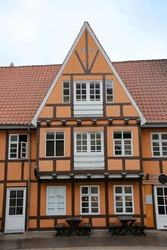 Historic and typical orange and wooden painted timbered building with white windows and doors in the city center, Aalborg, Denmark.