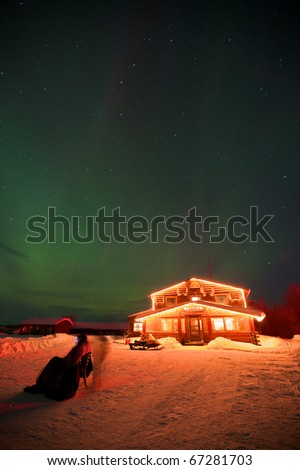 Historic Bettles Lodge in a snow-covered setting, brightly light under the Aurora Borealis.