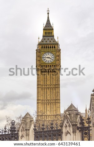 Historic Big Ben Tower with old clock giving the time against cloudy background #643139461
