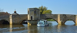 Historic bridge over the river Ouse at St Ives Cambridgeshire with river cruiser