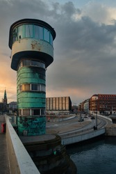 Historic bridge tower with dramatic sky and sunset in Copenhagen, Denmark. Cityscape in background, sun reflects in windows.