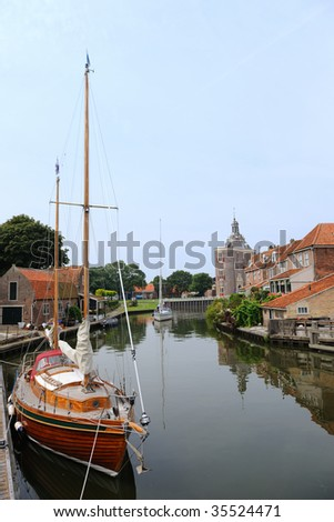 Historic building Dromedaris in Enkhuizen with sailboat - stock photo
