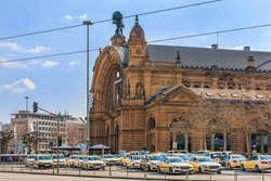 Historic building from the main train station in Frankfurt. Street with traffic lights and cars with a view of forecourt. Several taxis are waiting on the station forecourt