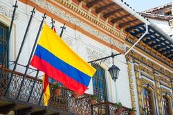 Historic buildings in Cuenca, Ecuador with a Ecuadorian flag in the foreground