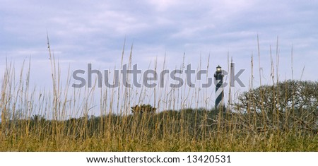 historic cape hatteras, nc lighthouse on cloudy morning with sea oats and dunes in foreground