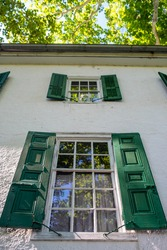 Historic colonial American home with beautiful woodwork and antique windows. Wooden dowel construction visible in frames, as well as wavy look of antique glass. Gorgeous 15-pane windows reflect the