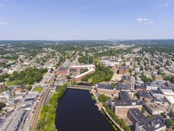 Historic Francis Cabot Lowell Mill building at Charles River and Waltham historic city center aerial view in city of Waltham, Massachusetts MA, USA.