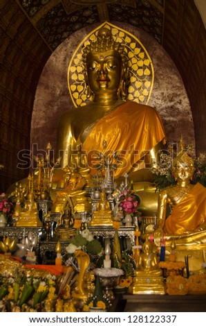 Historic golden Buddha surrounded by religious offerings at the temple of Wat Chet Yot, Chiang Mai, Thailand.