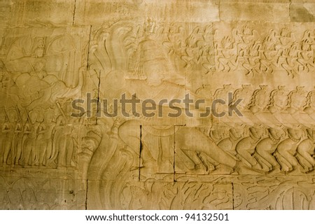 Historic Khmer carving showing the demons pulling on the sacred multi-headed snake known as Vasuki.  Hindu legend, the Churning of the Ocean of Milk, bas relief at Angkor Wat temple, Cambodia. - stock photo