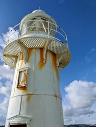 Historic lighthouse painted white with the contrast of bright orange rust from years of salt water and the elements battering the life saving beacon of light, represented in the sunlight and blue sky.