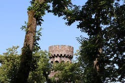 Historic medieval stone tower ruin and scenic palm trees of Quinta da Regaleira, Palace of Monteiro, old portuguese UNESCO tourism landmark attraction in Sintra near Lisbon (Lisboa), Portugal, Europe.