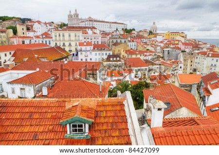 historic mediterranean architecture with small red roofs piled up houses and church in Lisboa, Portugal - stock photo