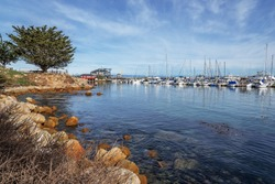 Historic Monterey Harbor and Marina; moored & anchored colorful sailboats, yachts, and speed boats. Located in the Monterey Bay National Marine Sanctuary, on California Central Coast, near Big Sur.