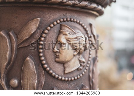 Historic ornaments and decoration on bronze - relif of profile of human face. Muted black and low depth of field #1344285980