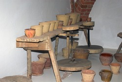 historic pottery workshop with clay pots in a room in the museum