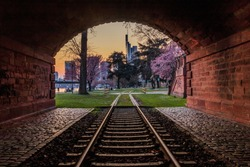 Historic railroad track with tunnel on the bank of the river Main in Frankfurt in the evening. Park with trees with blossoms and meadow. City skyline from the financial district in the background