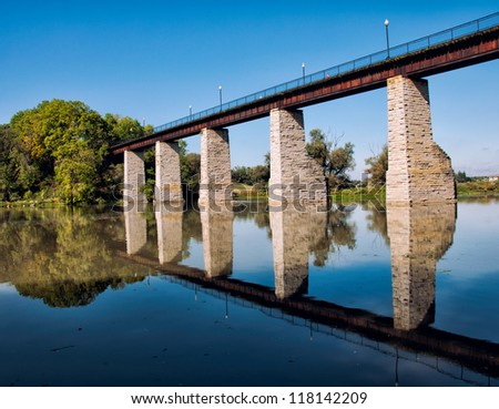 Historic railroad trestle over river with reflection in the river. - stock photo