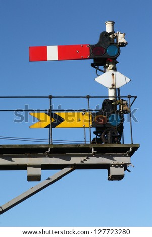 Historic red home and yellow distant railway signal.