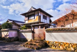 Historic residential house in traditional japanese architecture style surrounded by white wall with timber gate in remote village Ohara.