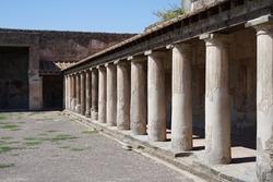 Historic Roman Bath with columns, Pompeii famous ancient city archaeological site near Mount Vesuv, popular tourist guided tour destination, Pompei, Italy