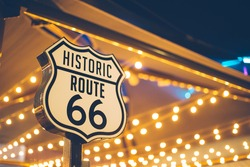 Historic Route 66 sign in California with decoration lights on the background