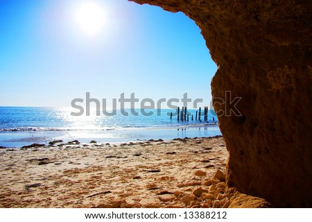 Historic ruined jetty at Port Willunga from a cliffside cave near Adelaide, Australia.