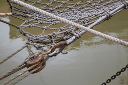 historic sailing ship with rigging and pulley on the bow of the boat