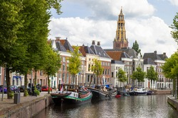 Historic ships, canal houses and warehouses on the old harbor at the Hoge der A with the tower of the historic Der Aa church in Groningen in the background.
