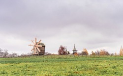 Historic site of wooden church and windmill of Kizhi Island, Republic of Karelia, Russia. Moody autumn landscape. The museum of wooden architecture.
