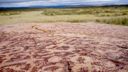 Historic spot in American Prairie. Land of Native Americans. Ancient symbols on a red stone. Montana