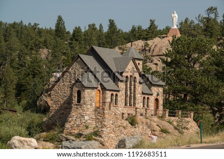 Historic St Malo Roman Catholic Chapel is also called Chapel on a Rock and St. Catherine of Siena Chapel, Allenspark, Colorado. Statue of Jesus Christ on hillside overlooking the chapel.