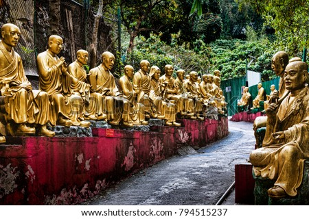 Historic Statues Lining Walkway to Buddhist Hilltop Monastery. Gold Statues of Arhat Buddha Monks along Path to Temple (Hong Kong, China).