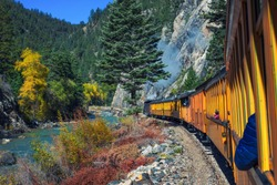 Historic steam engine train travels from Durango to Silverton through the San Juan Mountains along the Animas River in Colorado, USA.