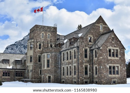Historic stone building with Canadian flag in Banff, Alberta