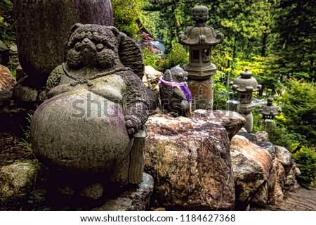 Historic Stone Tanuki Statue on Buddhist Mountain Path, with Forest Background and Toro Lanterns (Gifu, Japan).