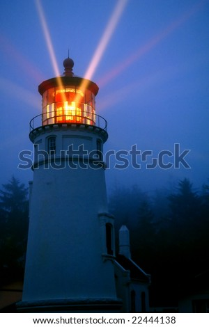historic umpqua lighthouse on oregon coast, actual beacon rays at twilight, two white and one red, long exposure